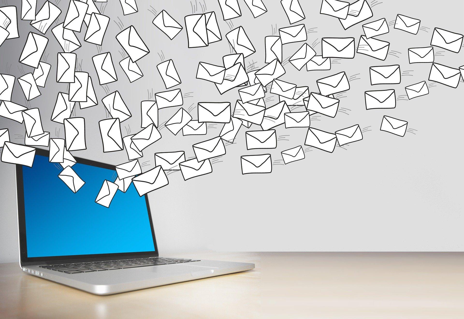 Computer mit vielen Emails die aus dem Bildschirm fliegen