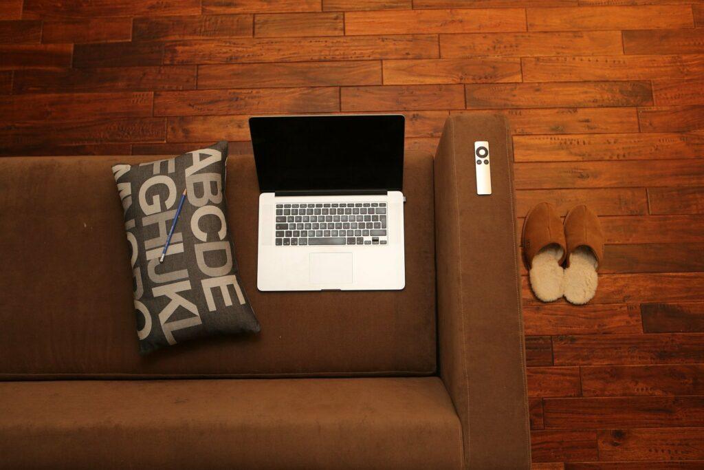 Laptop auf Couch. Neben Laptop ein Kissen auf dem ein Bleistift liegt. Rechts neben der Couch stehen Pantoffeln auf der Erde. Remotearbeit im Home Office